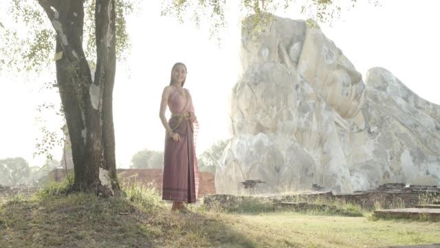 vídeos de stock, filmes e b-roll de dois jovens asiáticos falando no templo amcient tailandês no início da manhã com raios claros e neblina em antigo vestido estilo tailandês.4k câmera lenta. - blogar