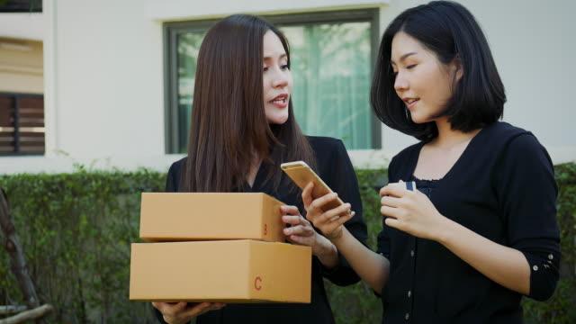 段ボール箱を持ち、屋外でスマートフォンを使用する2人の若いアジアの女性、中小企業の所有者やスタートアップの中小企業の起業家は、オンラインマーケティング包装ボックスの配達を働 - 受ける点の映像素材/bロール