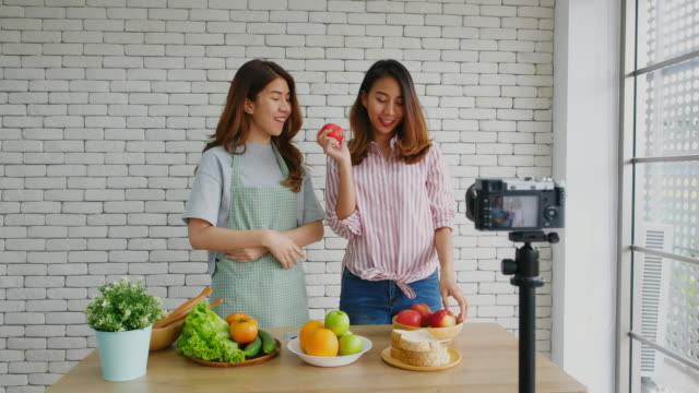 two young asian women food blogger holding red apple and explaining about healthy food for healthy lifestyle while recording video for broadcast, vlog healthy lifestyle - healthy eating stock videos & royalty-free footage