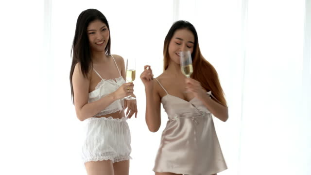 two young asian women friend or lesbian couple dancing and drinking wine in sexy nightwear on bed in the morning. - underwear stock videos & royalty-free footage