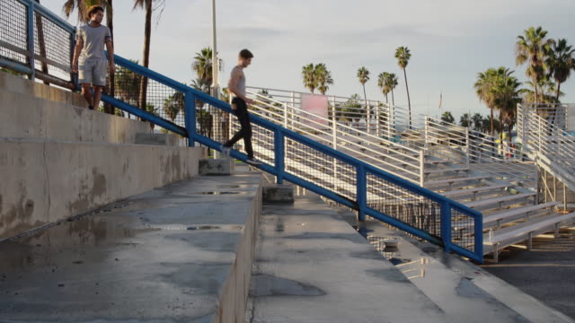 two young athletes, hispanic and caucasian white men, doing steps running on the outdoor public stadium, muscle beach, santa monica, california, usa - steps and staircases stock videos & royalty-free footage