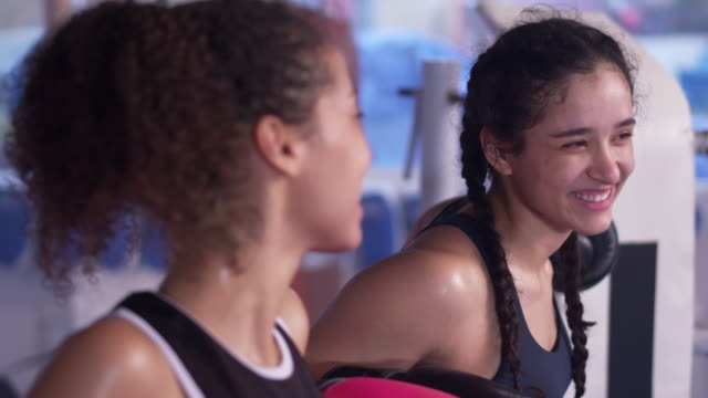 vídeos de stock e filmes b-roll de two young athletes resting in boxing ring after exercising - teenage girls