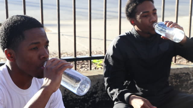 Two young basketball players drinking water while taking a break from playing.