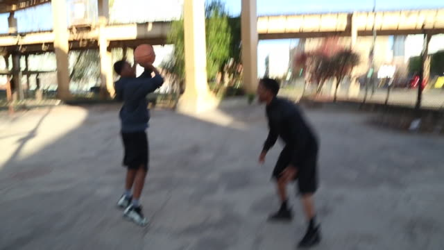 Two young basketball players playing one-on-one on a street basketball court.