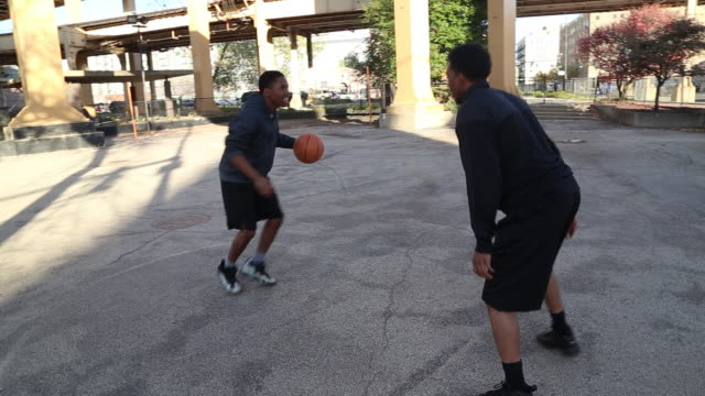 vidéos et rushes de two young basketball players playing one-on-one on a street basketball court.  - joueur de basket ball