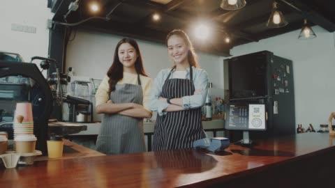 stockvideo's en b-roll-footage met twee jonge mooie aziatische vrouw barista wear schort praten en staan samen bij bar teller in coffeeshop met glimlach gezicht. concept van café en koffieshop kleine bedrijven. slow motion. - klanten georiënteerd