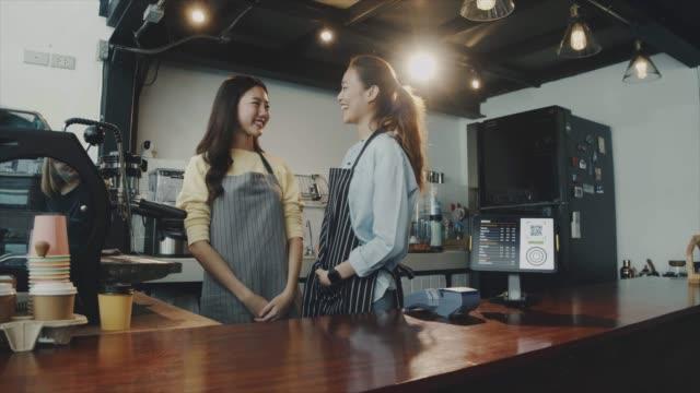 二人の若い美しいアジアの女性バリスタは、笑顔のコーヒーショップのバーカウンターで話し、一緒に立ってエプロンを着用します。カフェとコーヒーショップのスモールビジネスのコンセ� - ウェイトレス点の映像素材/bロール