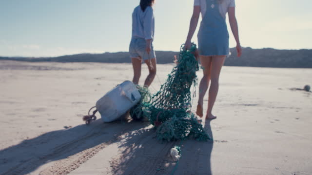 two young beautiful women collecting washed up trash on beach - müll stock-videos und b-roll-filmmaterial