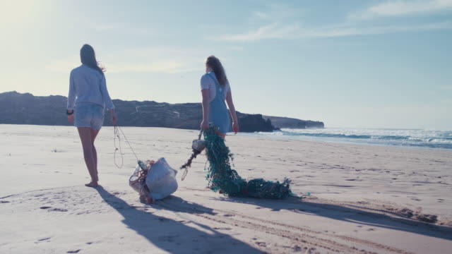 two young beautiful women collecting washed up trash on beach - sollevare video stock e b–roll
