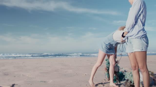 vídeos y material grabado en eventos de stock de two young beautiful women collecting washed up trash on beach - botella de agua