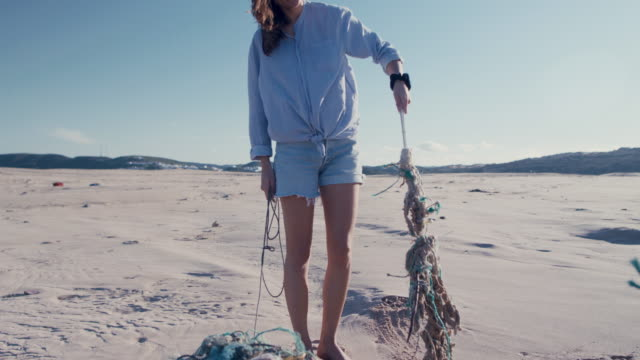 two young beautiful women collecting washed up trash on beach - pulizia dell'ambiente video stock e b–roll
