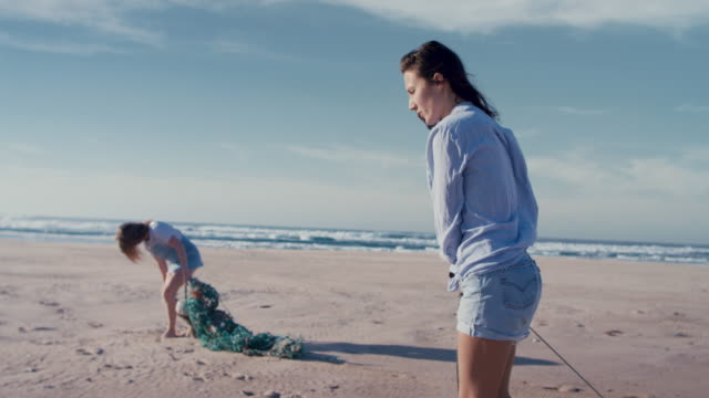 two young beautiful women collecting washed up trash on beach - material bildbanksvideor och videomaterial från bakom kulisserna