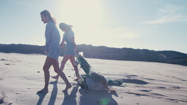 vídeos y material grabado en eventos de stock de two young beautiful women collecting washed up trash on beach - ecologista