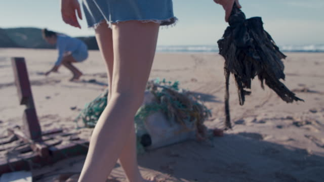 two young beautiful women collecting washed up trash on beach - verantwortung stock-videos und b-roll-filmmaterial