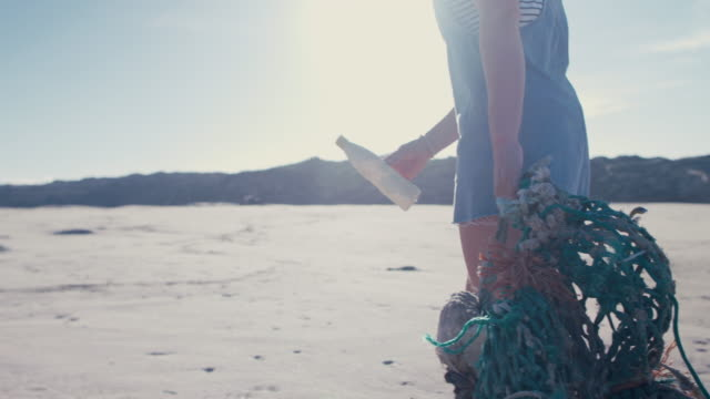 Two young beautiful women collecting washed up trash on beach