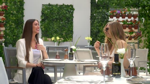 vídeos de stock, filmes e b-roll de duas jovens lindas sentadas em um restaurante de hotel de luxo se engajando em uma conversa jovial enquanto desfrutam de deliciosa sobremesa. - legal