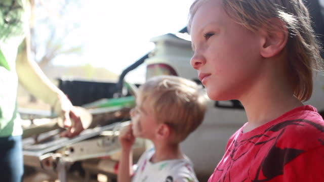 vidéos et rushes de two young boys and a woman at the back of their pickup truck, one young boy and the mother leave while the other boy wipes his face - kelly mason videos
