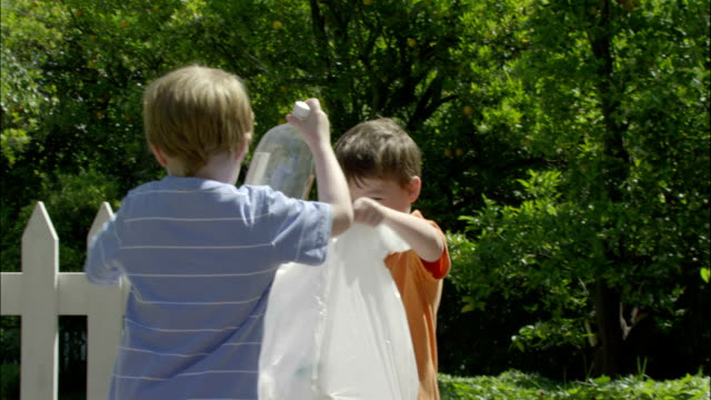 two young boys bag up plastic bottles for recycling. - chores stock videos and b-roll footage