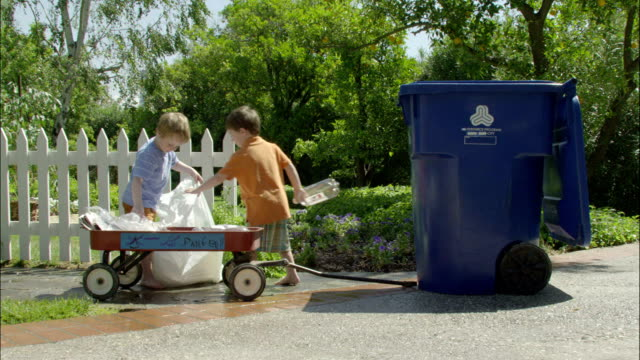 two young boys dump plastics into a recycling bin. - chores stock videos and b-roll footage