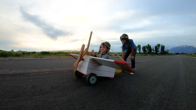 two young boys flying vintage toy plane - copy space stock videos & royalty-free footage