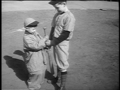 b/w 1941 two young boys in baseball uniforms holding baseball bat / nyc / newsreel - baseball bat stock videos & royalty-free footage