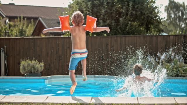 slo-mo ds zwei jungen springen sie in den pool - schwimmflügel stock-videos und b-roll-filmmaterial