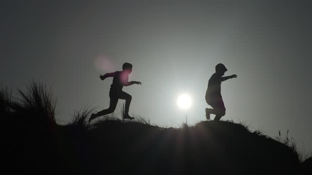 two young boys leaping, running and racing each other across sand dunes at sunset. - in silhouette stock videos & royalty-free footage
