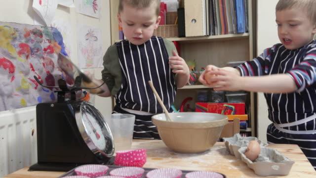 stockvideo's en b-roll-footage met two young boys making cakes together on kitchen table full of excitement  - tanden op elkaar klemmen
