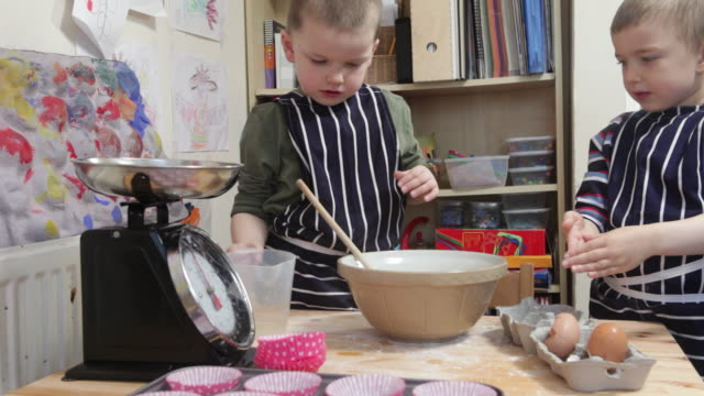 Two young boys making cakes together on kitchen table full of excitement