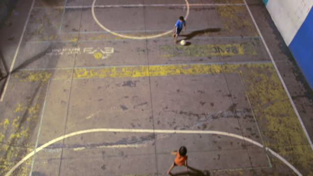 HIGH ANGLE TILT DOWN two young boys play soccer on cement field at night