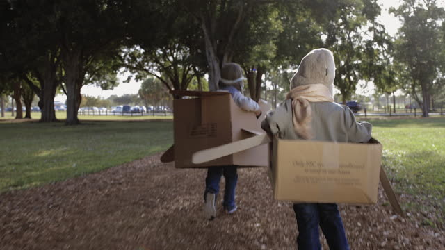 TS Two young boys playing in cardboard aeroplanes racing each other away from camera