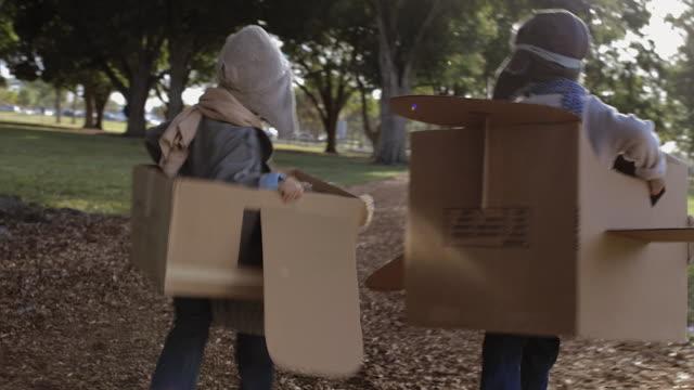 vídeos de stock, filmes e b-roll de ts two young boys playing in cardboard aeroplanes racing each other - caixa de papelão