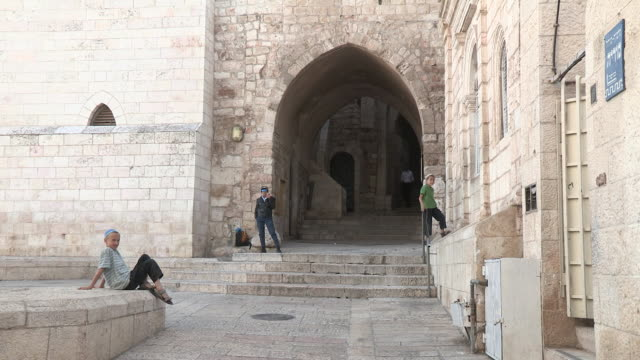 Two young boys playing near an archway with other peds NO