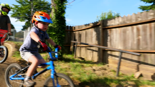 pan two young boys riding bmx bikes on backyard dirt track together on summer afternoon - sibling stock videos & royalty-free footage