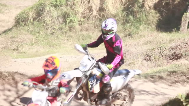 vidéos et rushes de two young boys riding their dirt bikes on a dirt bike track while a woman follows them on a sunny summer day - kelly mason videos