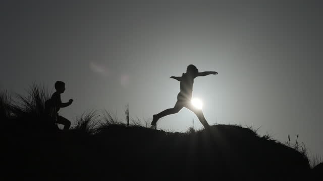 two young boys running and leaping across sand dunes. - silhouette stock videos & royalty-free footage