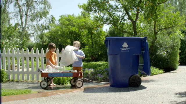 two young boys throw a plastic bag into a recycling bin. - bin bag stock videos & royalty-free footage