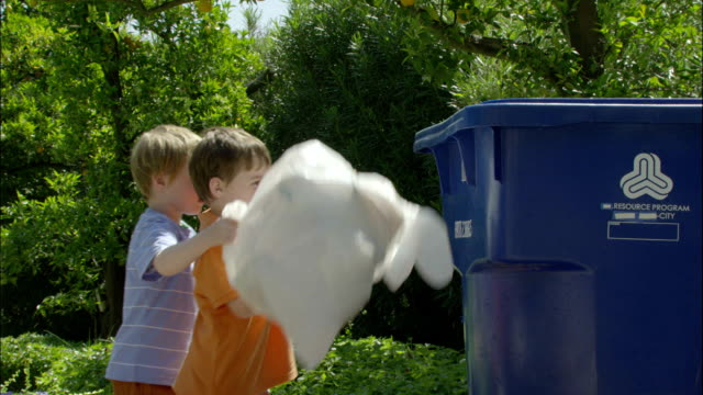 two young boys throw plastic bottles and bags into a recycling bin. - bin bag stock videos & royalty-free footage