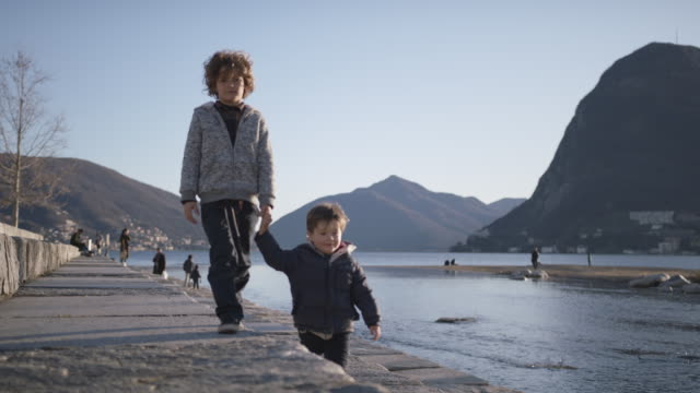 two young boys walking together along river holding hands - brother stock videos & royalty-free footage