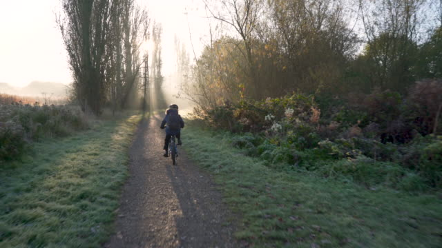 two young brothers cycling to school - richtung stock-videos und b-roll-filmmaterial