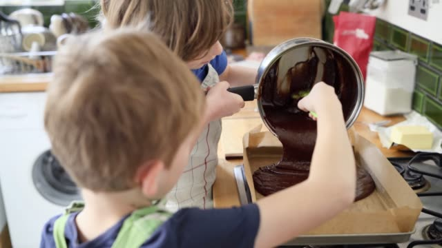 two young brothers helping one another pour chocolate brownie mix into a baking tray - baking tray stock videos & royalty-free footage