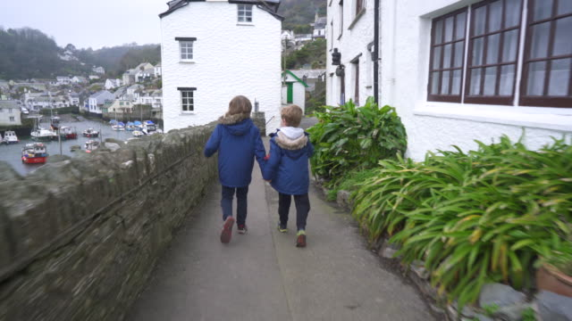 Two young brothers walking near a harbour