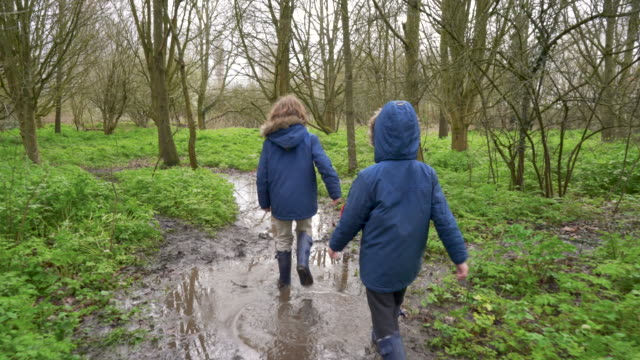 two young brothers walking through a puddle - mud stock videos & royalty-free footage