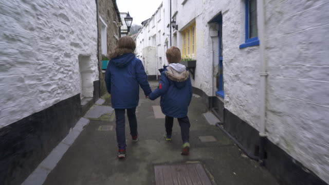 two young brothers walking through an old fishing village - 40 o più secondi video stock e b–roll
