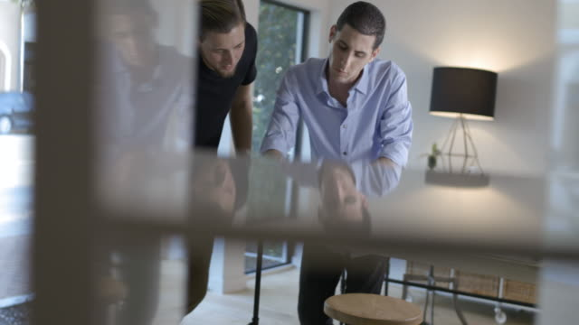 WS Two young business men at desk in modern office developing business project