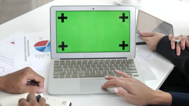vidéos et rushes de deux personne de young business talking business sur ordinateur portable avec écran vert - tenue d'affaires formelle