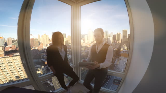 two young business professionals talking together staning on window front in modern city office building