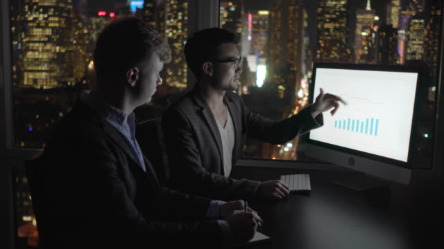 two young businessman having a business meeting analyzing charts on computer screen talking together