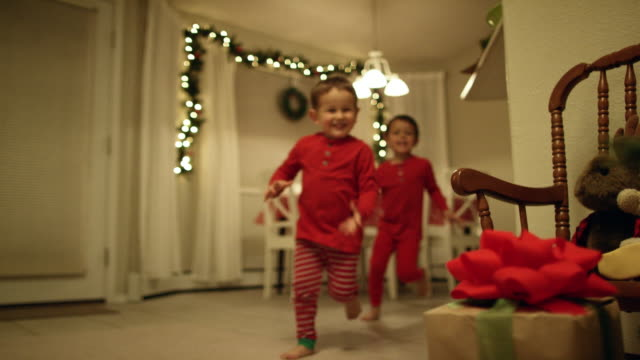 two young (three and five year-old) caucasian boys in pajamas run to the christmas tree and excitedly pick up christmas presents from underneath the christmas tree on christmas day - christmas gift stock videos & royalty-free footage