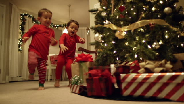 two young (three and five year-old) caucasian boys in pajamas run to the christmas tree and excitedly pick up christmas presents from underneath the christmas tree on christmas day - christmas stock videos & royalty-free footage